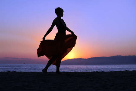 Woman walking on the beach at sunset