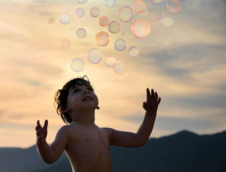 blowing bubbles: Little boy trying to catch some soap bubbles
