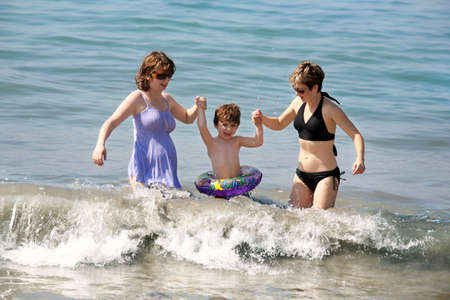 lesbiana: Dos mujeres y un beb� jugando en el oc�ano