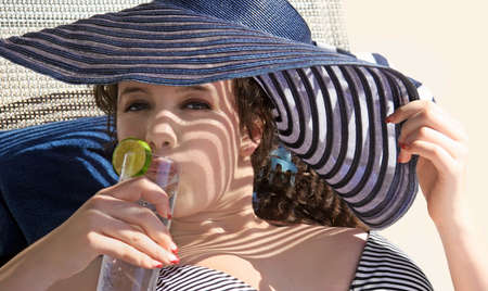 Gorgeous teen girl drinking water on the beach photo
