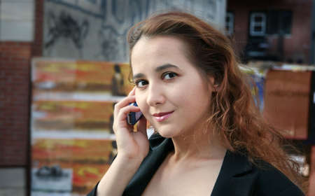 A young woman talking on the phone in the city photo