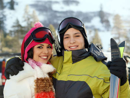 Young happy couple in winter clothes and gogles in skiing resort Stockfoto