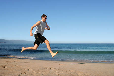 Barefooted man running on the beach photo