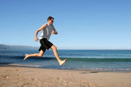 barefoot: Hombre corriendo descalzo en la playa Foto de archivo
