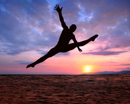 A silhouette of a jumping man on a colorful sunset background photo