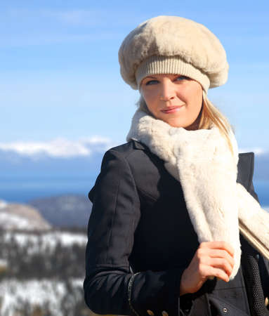 Blond girl in a fur hat and a scarf photo