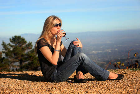 A young blond woman tasting wine outdoors photo