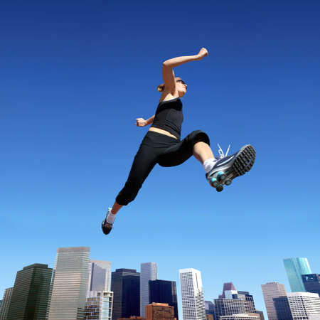 A young blond woman jumping high above downtown