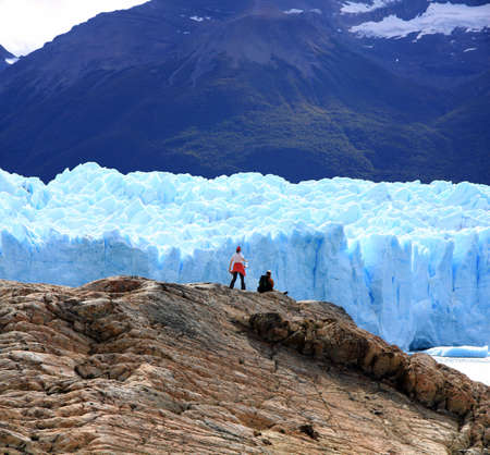 Couple looking at Perito Moreno Glacier, Patagonia, Argentina photo