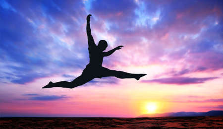 A silhouette of a jumping man on a colorful sunset background