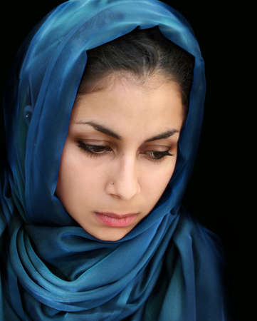 A portrait of a young arab woman in a blue scarf