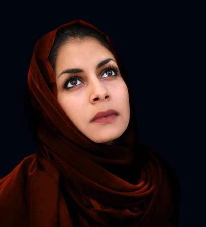 middle eastern clothing: Un ritratto di una giovane donna araba in una sciarpa rossa intorno al collo