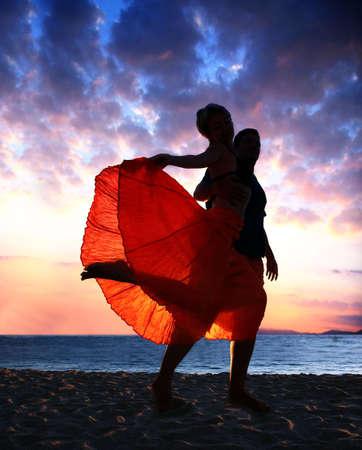 A couple enjoying sunset on the beach Stock Photo - 4611034