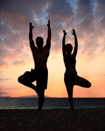 Couple doing yoga exercise on the beach Stockfoto