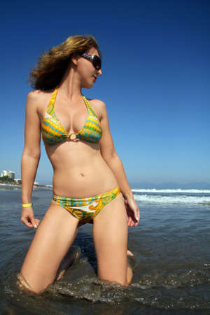 A young woman standing in the water on the beach photo
