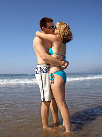 A young kissing couple on the beach