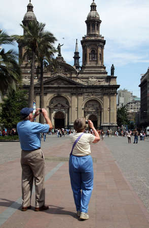 Couple of tourists taking pictures at Plaze de Armas in Santiago, Chile