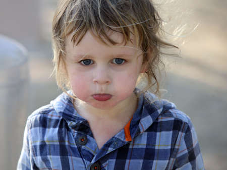 A close-up of a cute sad baby boy photo