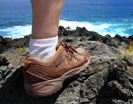A foot of a hiker standing on a lava coast of Easter Island Stockfoto