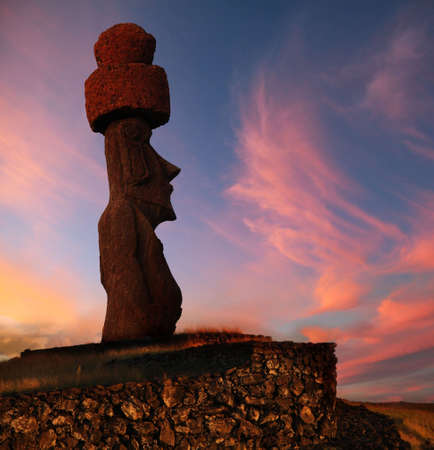 A stone statue on Easter island at sunset