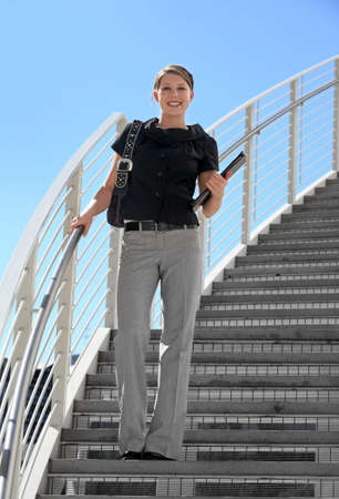 A young business woman standing on the staircase Stock Photo - 4723390