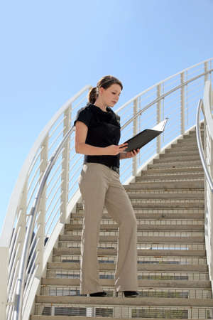 A young business woman standing on the staircase