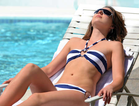 recline: A young pretty Girl sunbathing by the pool