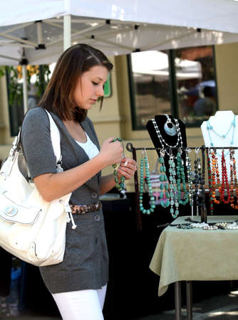 A teenage girl looking at gemstone necklaces at the market Stockfoto