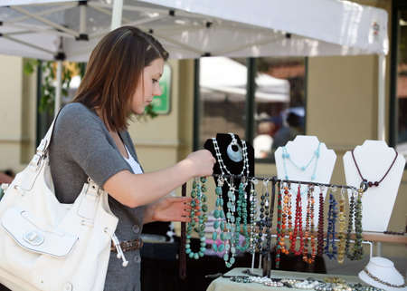 A teenage girl looking at gemstone necklaces at the market Standard-Bild