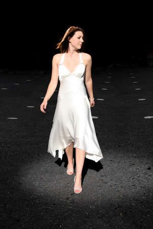 A young woman in a white dress walking on a black background