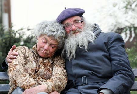 hombre pobre: Un viejo cpuple sin hogar durmiendo en un banco Foto de archivo