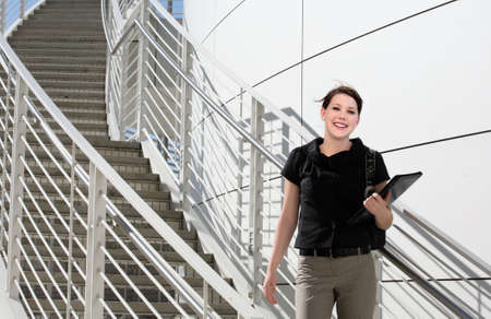 A young business woman standing on the stairs