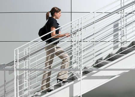 A girl college student walking up the staircase