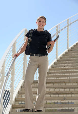 A young business woman standing on the staircase Stock Photo - 4889199