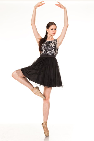 Beautiful young ballerina, isolated on white background. In pointes and black ballet tutu. Sits on the twine, shows different poses. graceful brunette with long hair Stock Photo