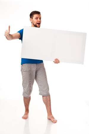 A guy with a beard posing with a white sign. Shows different emotions. Isolated on a white background. In a gray trousers and a blue T-shirt. For advertising, logo, business cards, contact phones, etc