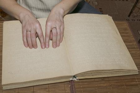 Blind man reads Braille book photo