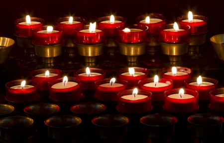 Rows of red wax lights in Roman Catholic church