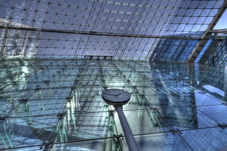 db: Berlin, Germany - May 20, 2012: clock in front of glass facade of Berlin Central Station  Berlin Hauptbahnhof, backlit by sun