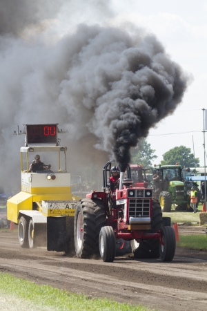 Zelhem, Netherlands - June 17, 2012: Black smoke from International tractor starting in Super series at Tractor Pulling contest Oosterwijk near Zelhem, Netherlands