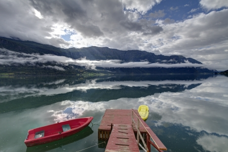 Double layer of clouds above Sognefjord, Norway, reflected in water with rowing boatss with sunbeams through hole in the cloud, reflected in the water