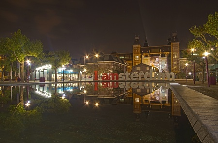 Amsterdam, Netherlands - October 17, 2012: Rijksmuseum and I Amsterdam sign reflected in pool at night