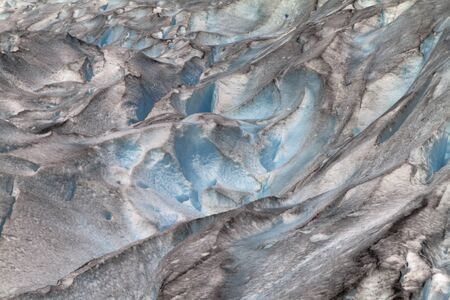 jostedal: Glacier crevasses in Norway, Jostedalsbreen. Close up showing abstract pattern of blue ice, dirt and melting water caused by climate change  Stock Photo