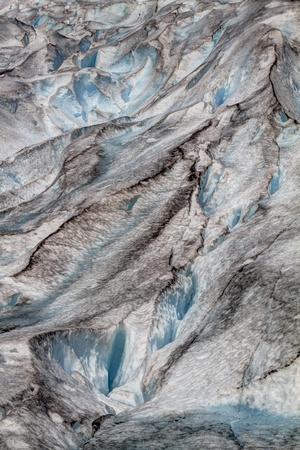 breen: Crepacci del ghiacciaio in Norvegia, Jostedalsbreen. Close up in verticale mostrando modello astratto di ghiaccio blu, sporco nero e l'acqua di fusione causata dal cambiamento climatico