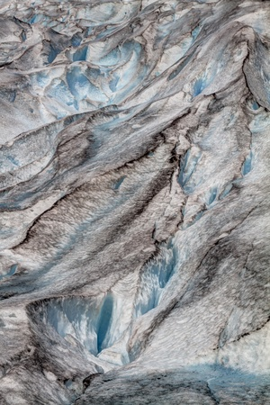 Glacier crevasses in Norway, Jostedalsbreen. Close up in portrait showing abstract pattern of blue ice, black dirt and melting water caused by climate change