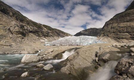 breen: Ghiacciaio di fusione con rapide nel contesto drammatico di montagne a forma di V sulla chiara giornata di sole in Norvegia, Jostedalsbreen. HDR foto con lunga esposizione per ammorbidire il flusso dell'acqua