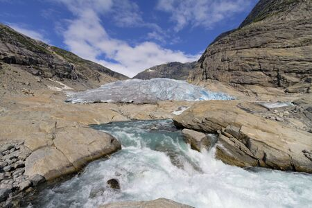 Melting glacier with rapids in dramatic setting of mountains on clear sunny  day in Norway, Jostedalsbreen photo