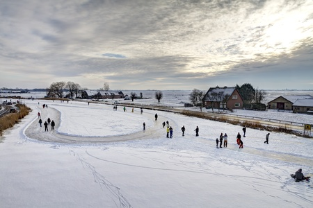 Ouderkerk aan de Amstel, the Netherlands, February 2, 2012 - Skaters on cleared skating rink with return point on frozen river Bullewijk during sunset