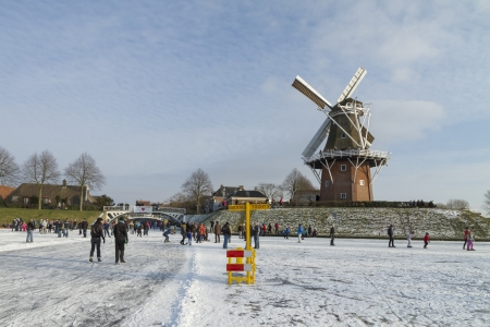 Dokkum, Friesland, the Netherlands, February 11, 2012 - Ice skaters on frozen canals, skating a signposted tour with old windmill Zeldenrust and rampart on the background
