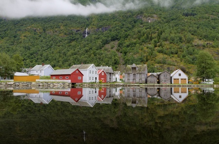 Laerdalsoyri, Norway, August 19, 2012 - Old wooden houses of Laerdalsoyri brightly reflected in still water with forest and waterfall Editorial